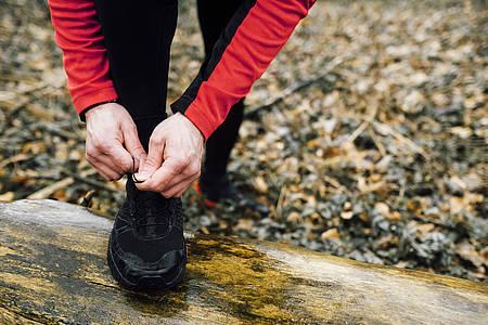 Joggerin schnürt sich auf Baumstamm die Laufschuhe zu