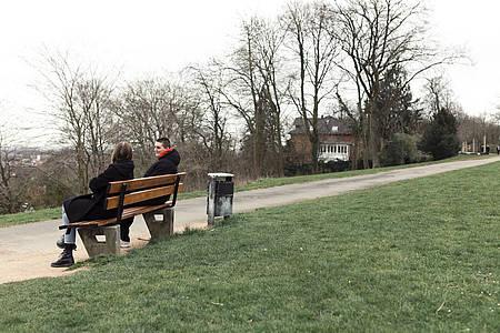 Zwei Menschen sitzen einsam auf einer Bank im Park