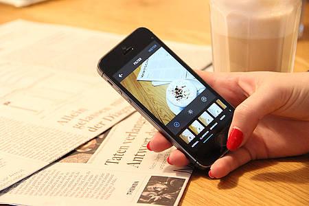 Hand mit roten Fingernägeln bearbeitet Instagram-Posting mit Kaffeetasse drauf