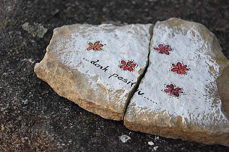 Mit Blumen bemalter Stein auf dem denk positiv steht