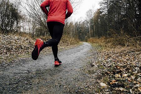 Typ in rotem Shirt joggt auf Waldweg