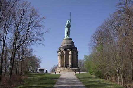 Ein Weg führt gesäumt von Bäumen zu einer Statue