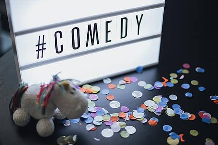 Gehäkeltes Pummel-Einhorn sitzt m Konfetti vor Lightbox mit dem Schriftzug #Comedy