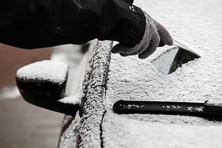 verschneite Autoscheibe wird freigekratzt