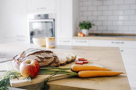 Küchenzeile mit einem Leib Brot und Gemüse im Vordergrund